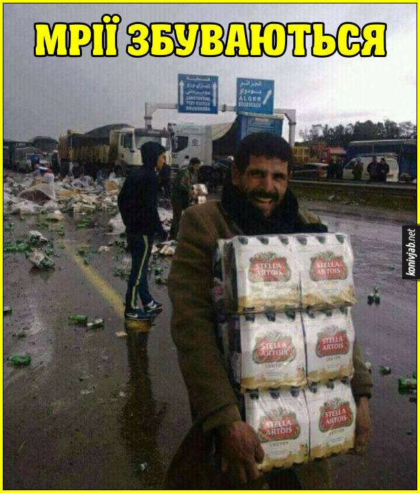 Перекинулася вантажівка з пивом. Один чоловік схопив кілька ящиків з пивом і радісно втікає. Смішне фото про мародера