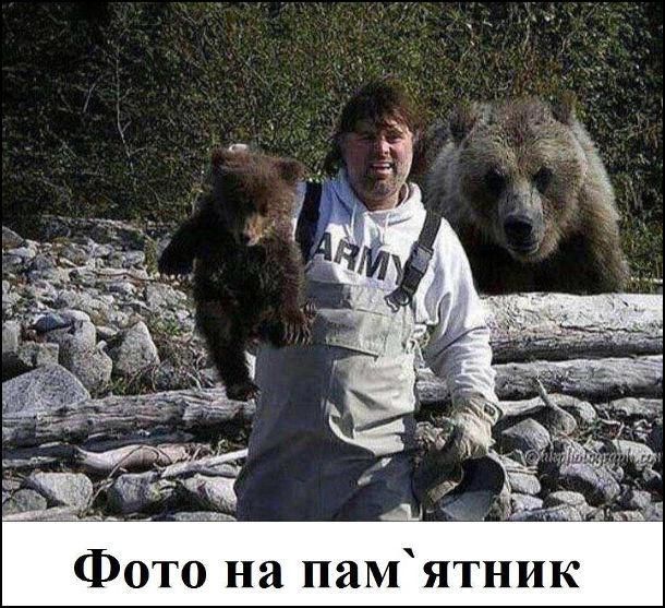 Прикол. Чоловік робить фото з ведмежам, тримаючи його за шкірки, а в цей час до нього ззаду наближається ведмедиця (мати ведмежати). Судячи з усього це буде фото на пам'ятник