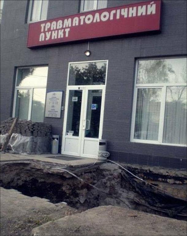 Смішне фото в місті. Травматологічний пункт, перед дверима якого вирита яма. Можна впасти в яму і одразу в травматологію