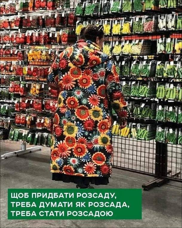 Прикол Куртка. Жінка в куртці з квітками вибирає на лотках насіння для садіння майже зливається з навколишнім середовищем (яскравими пакетиками з насінням). Щоб придбати розсаду треба думати як розсада, треба стати розсадою