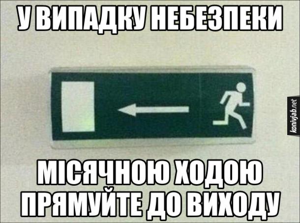 Прикол табличка, де вказується рух до аварійного виходу, але при цьому зображено людину, що біжить в інший бік. У випадку небезпеки місячною ходою прямуйте до виходу