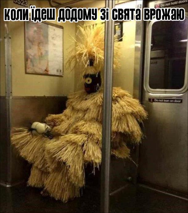 Дивак в метро в якомусь африканському етнічному костюмі, зробленому з соломи. Коли їдеш додому зі свята врожаю